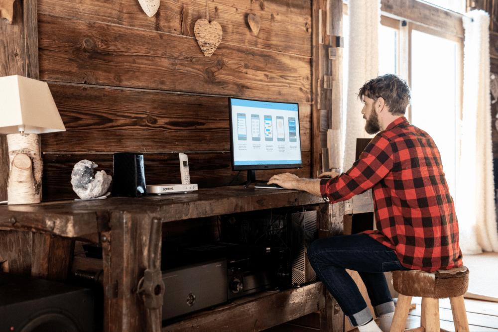jeune homme travaillant devant son ordinateur dans sa maison de campagne