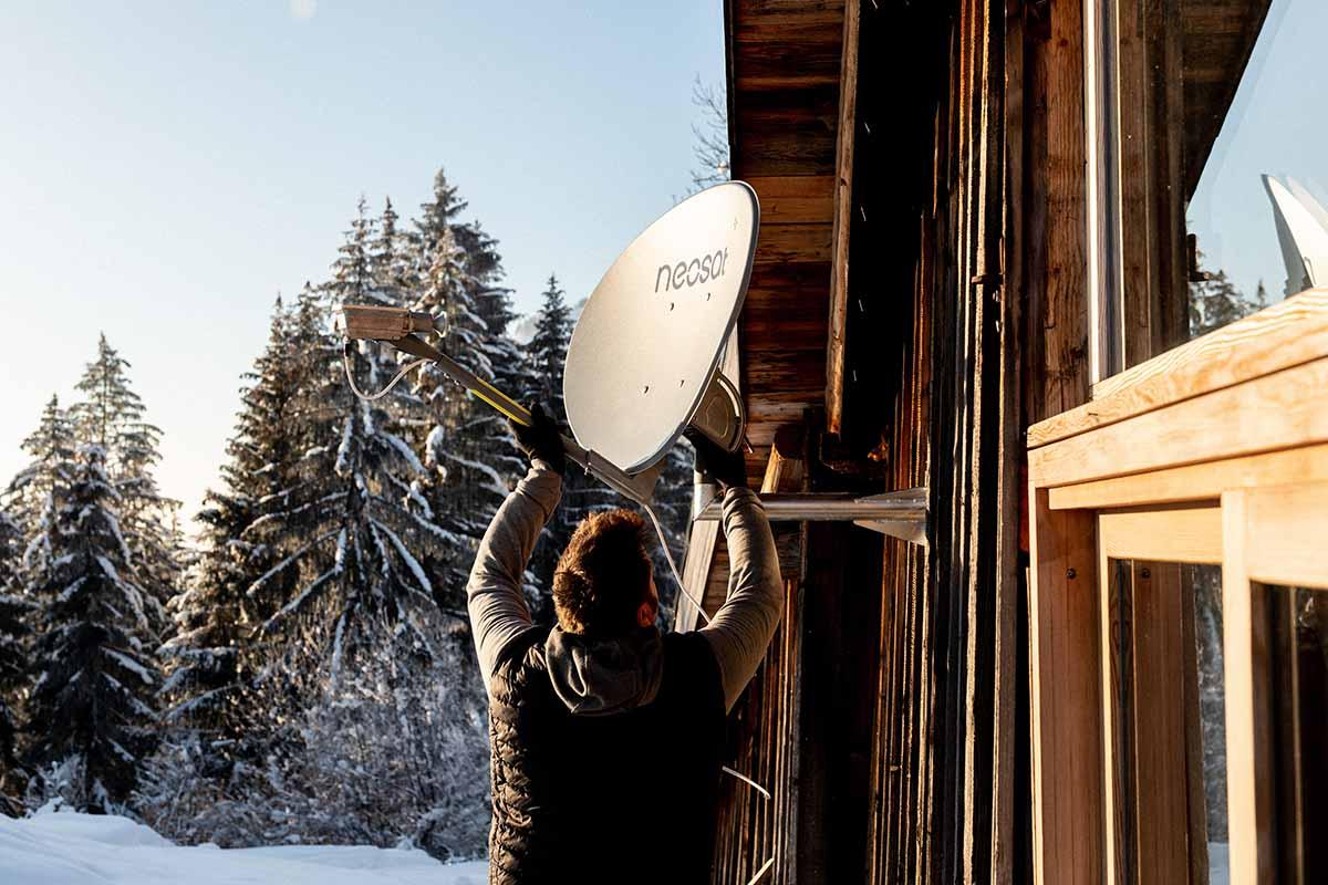 homme installant une parabole neosat de nordnet sur le mur d'une maison de haute montagne, paysage enneigé